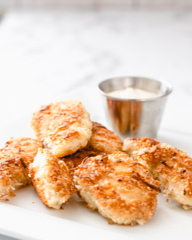 Close up view of coconut chicken strips on a plate with a ramekin of ranch dressing.