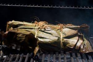 Kalua pork wrapped in banana leaves on smoker