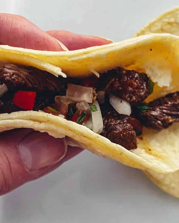A hand holding a street taco with fresh pico de gallo.