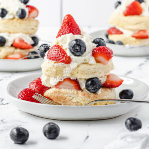 Strawberry blueberry shortcake on a plate, with a fork on the plate, and 2 more shortcakes on plates in the background.