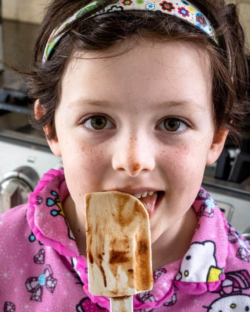 Girl licking brownie batter off a spatula
