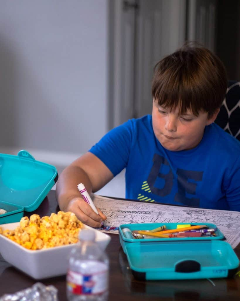 Boy coloring a state facts sheet with popcorn in front of him.
