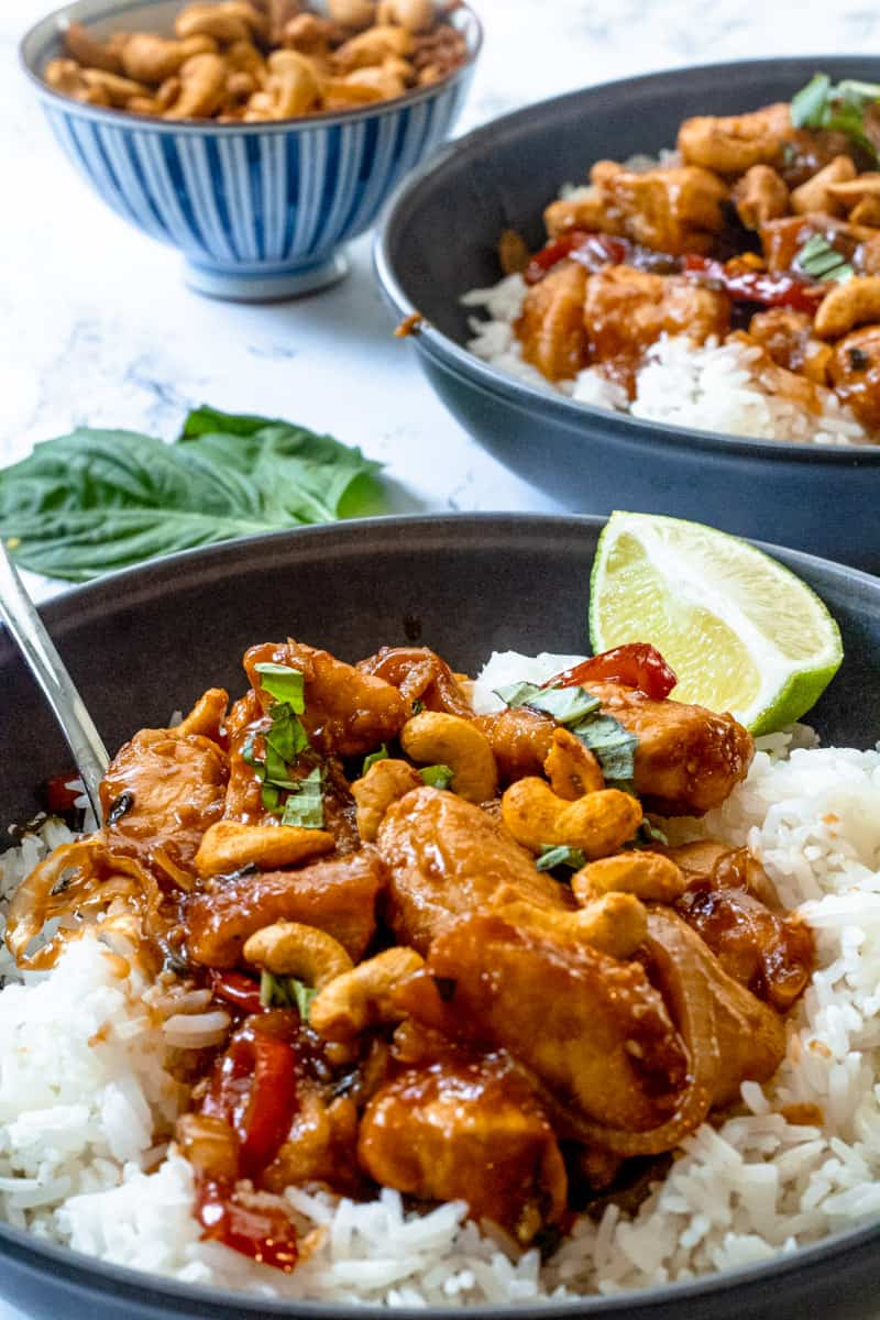 Two bowls of Thai cashew chicken with small bowl of cashews