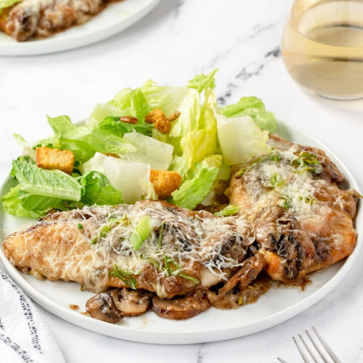 Chicken lombardy on a plate with caesar salad and a glass of white wine.