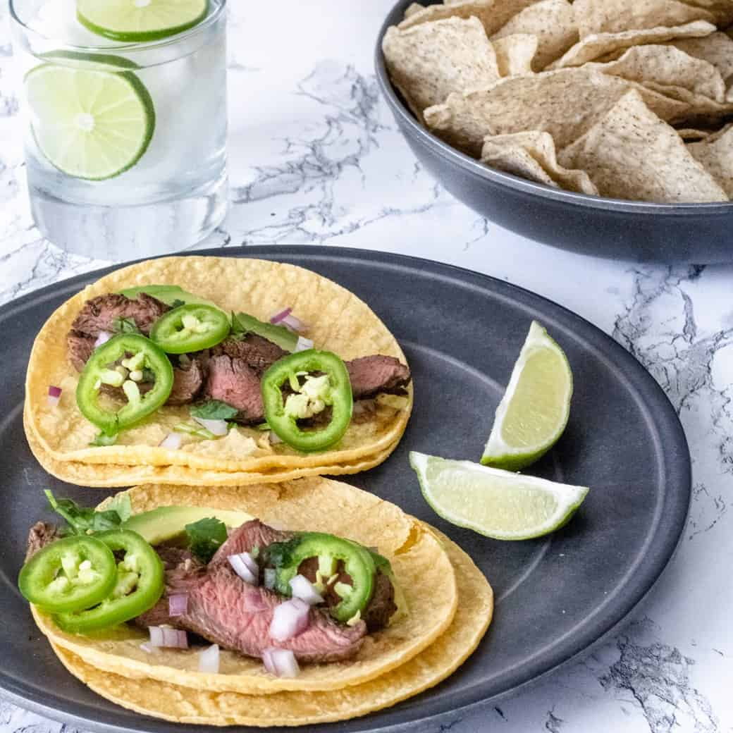 Simple Steak Tacos on plate with a bowl of chips