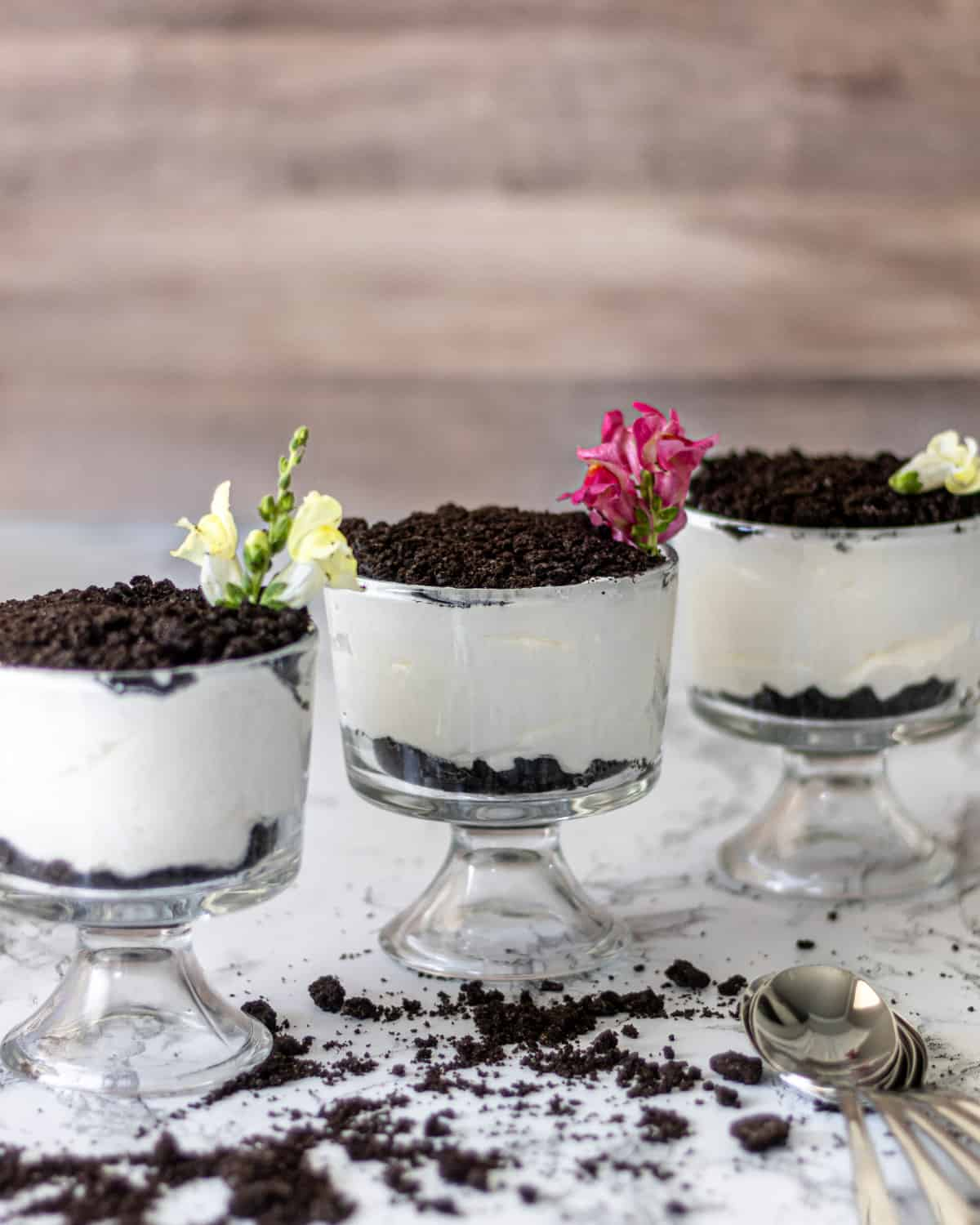 3 individual bowls of Kansas dirt cake with snapdragons on top. Crumbs on the counter and spoons in the corner.