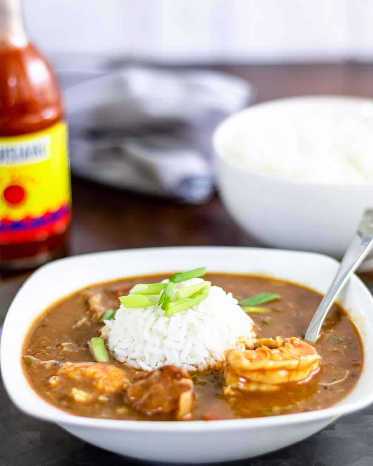 Bowl of shrimp and sausage gumbo with rice in the middle. Louisiana hot sauce and bowl of rice behind.