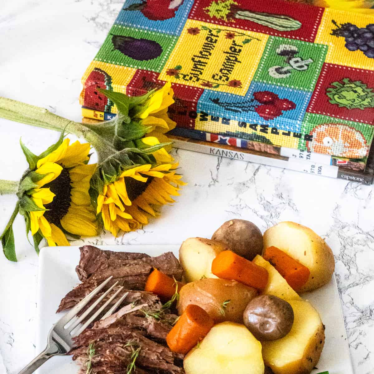 Plate of roast beef with carrots, potatoes & mushrooms. Sunflowers and cookbooks in background.