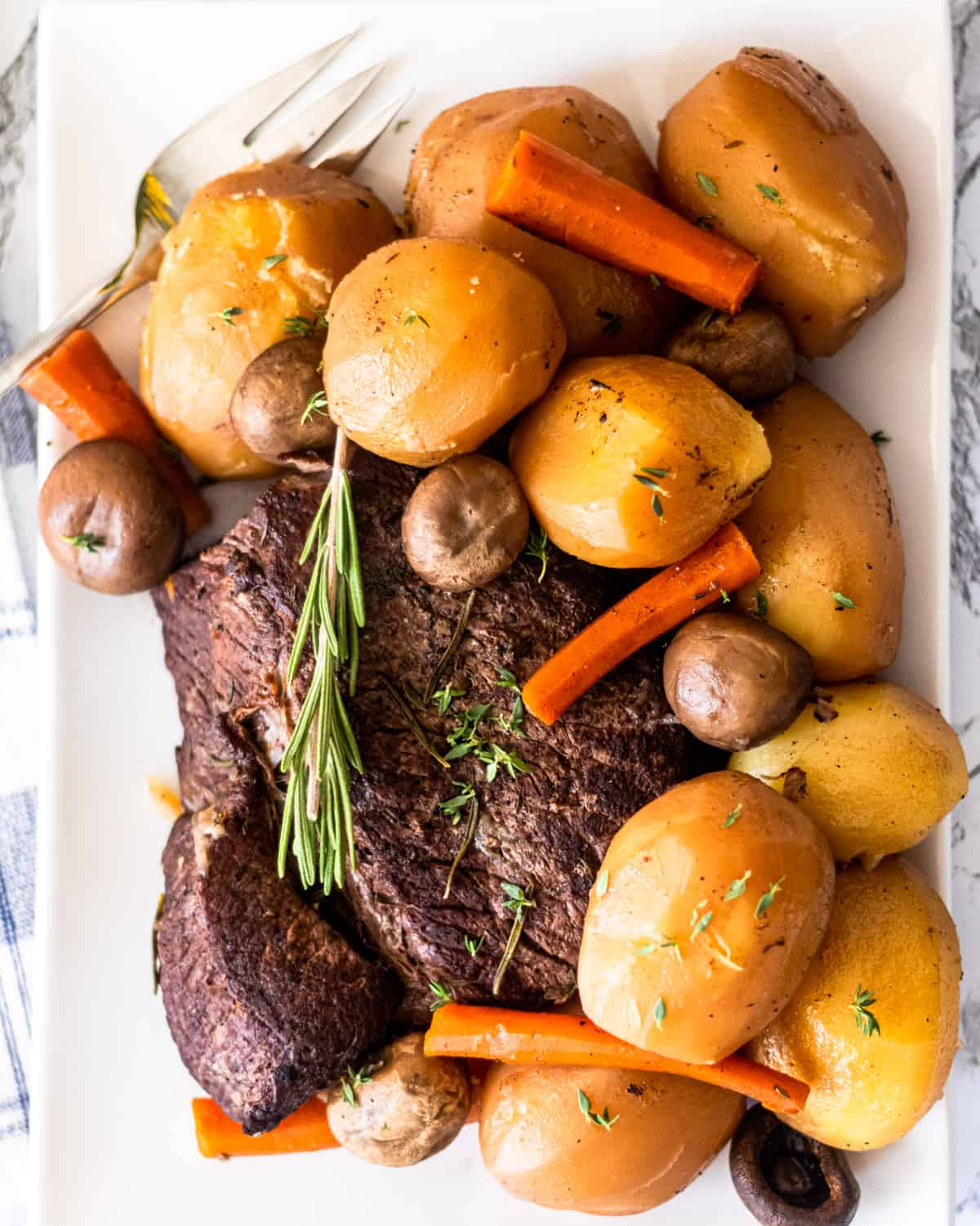 Overhead shot of a platter of pot roast, with potatoes, carrots, mushrooms and sprigs of rosemary and thyme