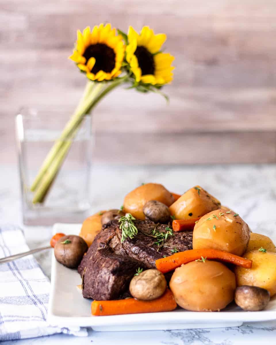 Plate of roast beef with potatoes, carrots and mushrooms piled on top. Sunflower in vase in background.