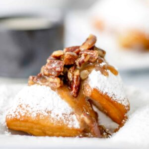 2 pecan praline beignets with a cafe au lait in the background.