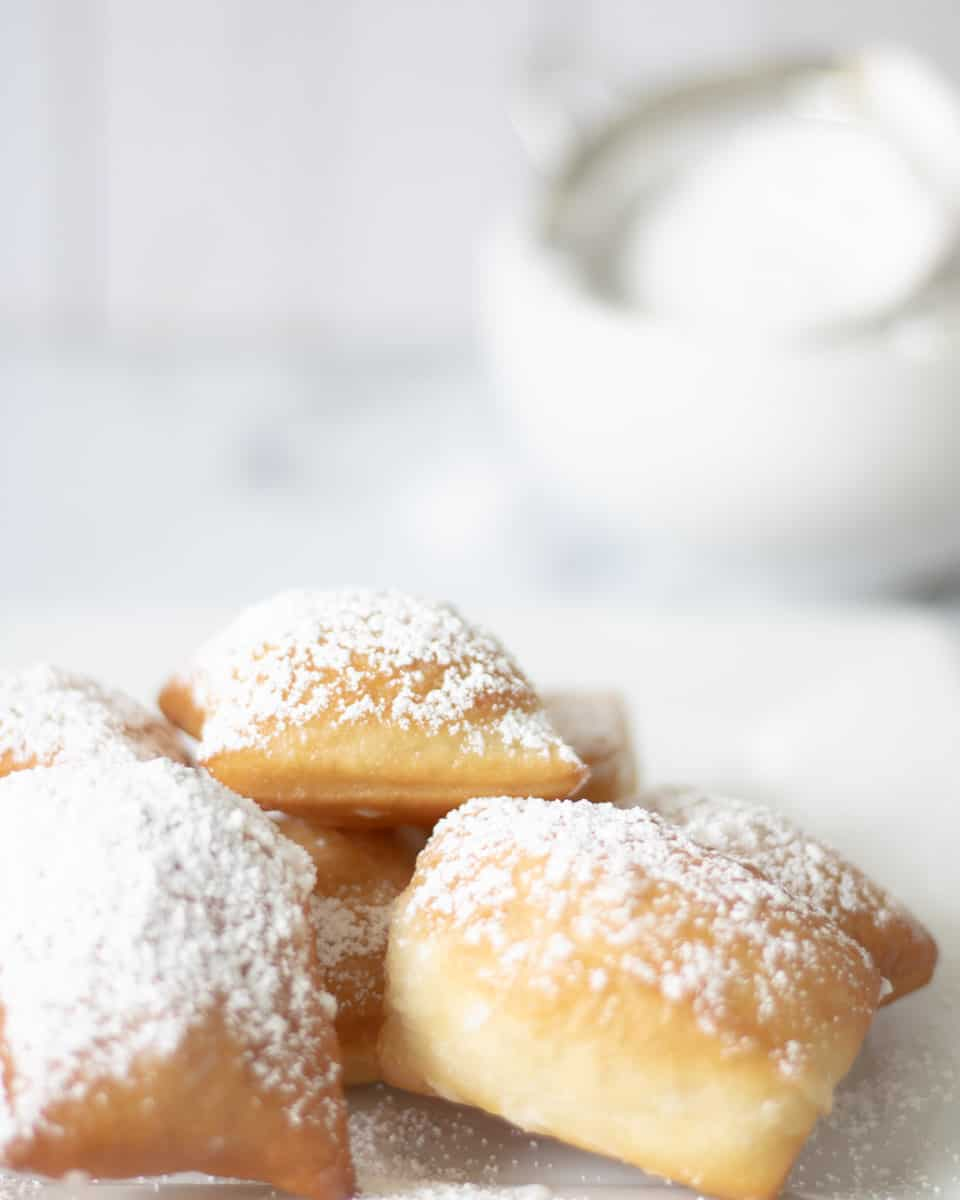 Plate of beignets lightly dusted with powdered sugar. Bowl of powerdered sugar with sifter in background.