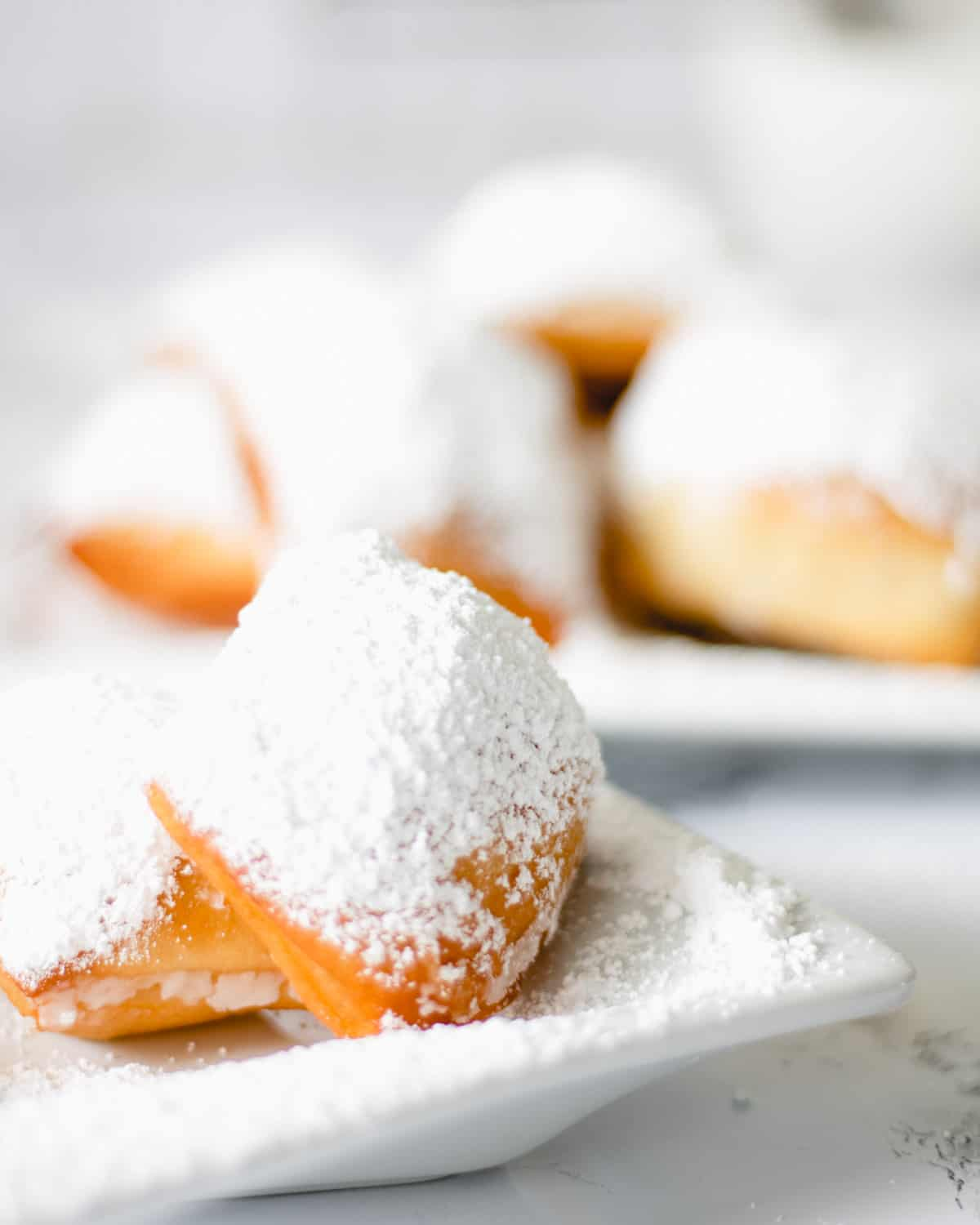 Two plates of beignets covered in powdered sugar.