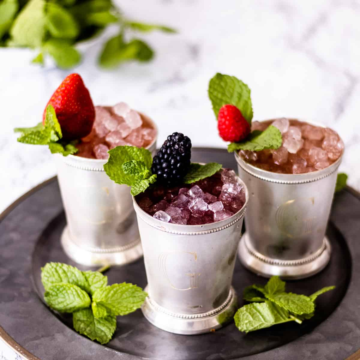 3 cups of berry mint juleps on a tray, with mint in the background.