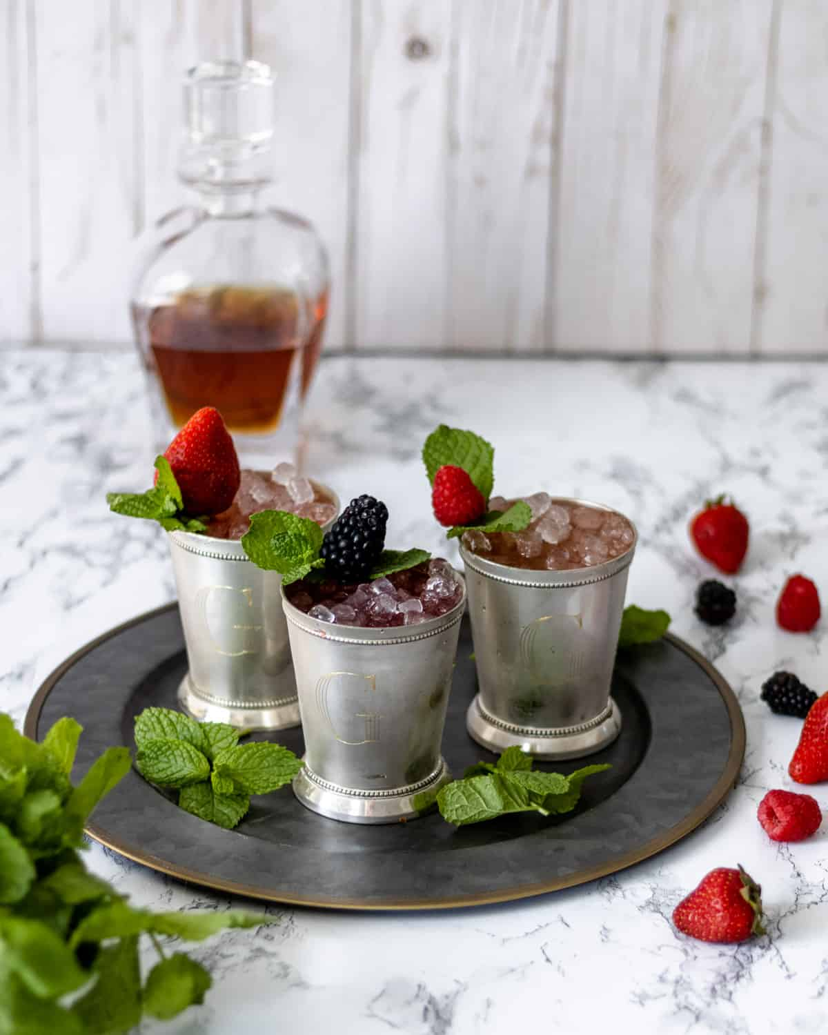 3 berry mint juleps with berries and mint scattered around.