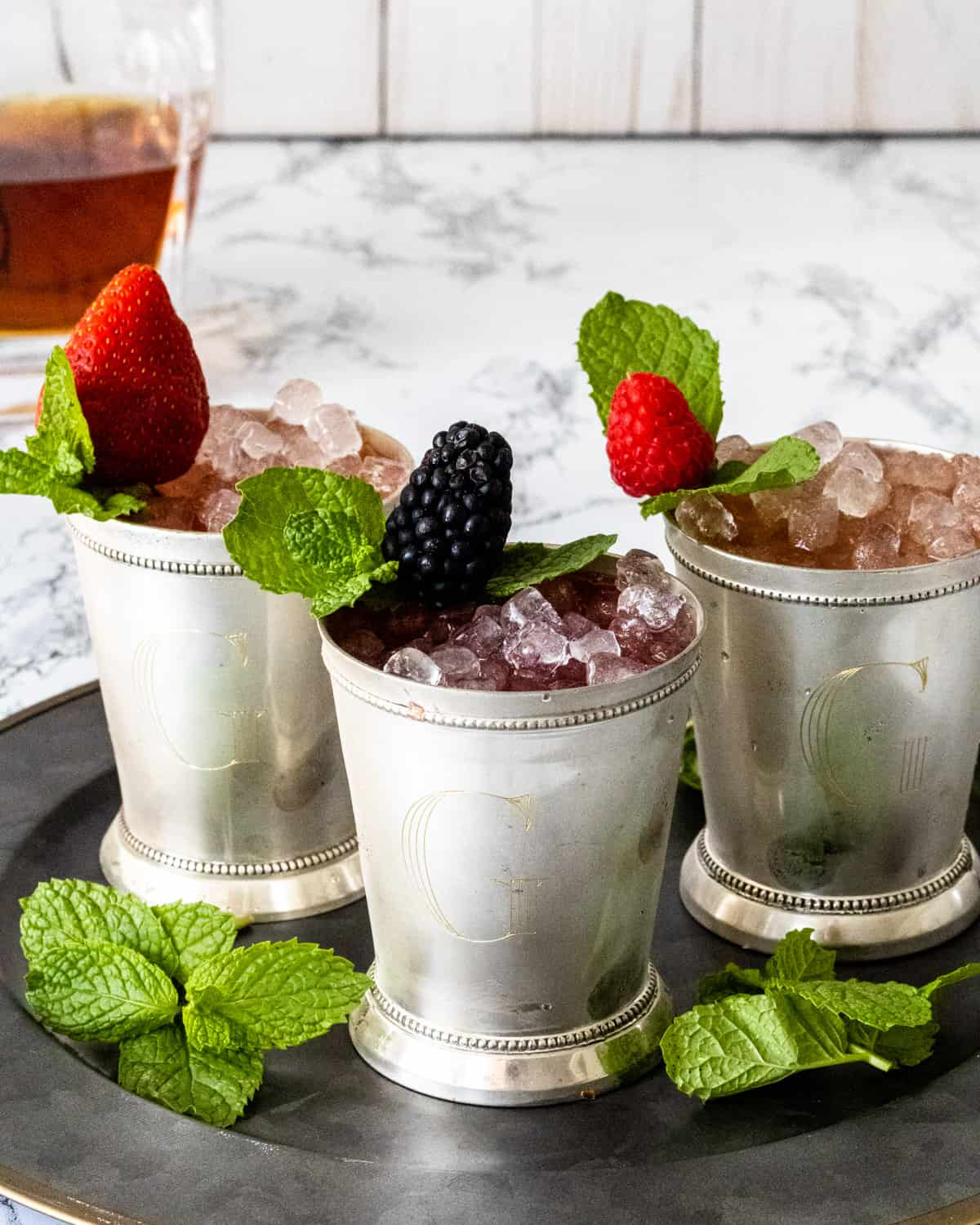 3 berry mint juleps on a tray with whiskey in background.