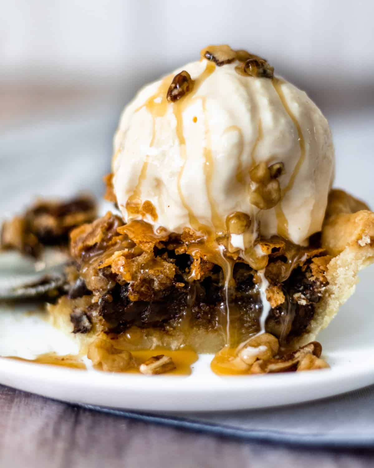 slice of chocolate walnut pecan pie with ice cream on top and caramel drizzled all over.