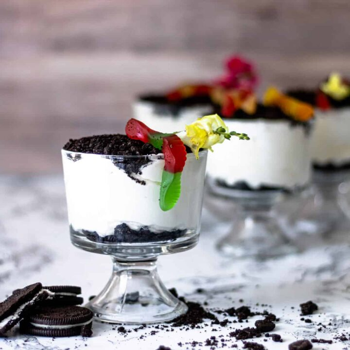 4 parfait glasses with pudding topped with Oreos. Gummy worms and flowers on top, and Oreos stacked on the side.