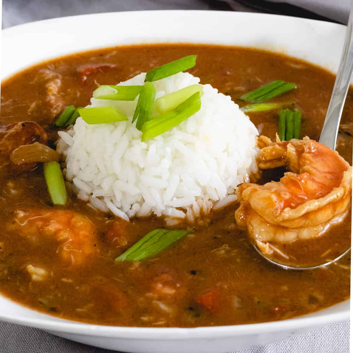 Bowl of louisiana gumbo with a ball of rice in the middle. Spoon is scooping up a piece of shrimp.