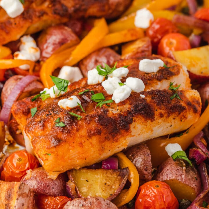 Close up of mediterranean cod on sheet pan of roasted vegetables.