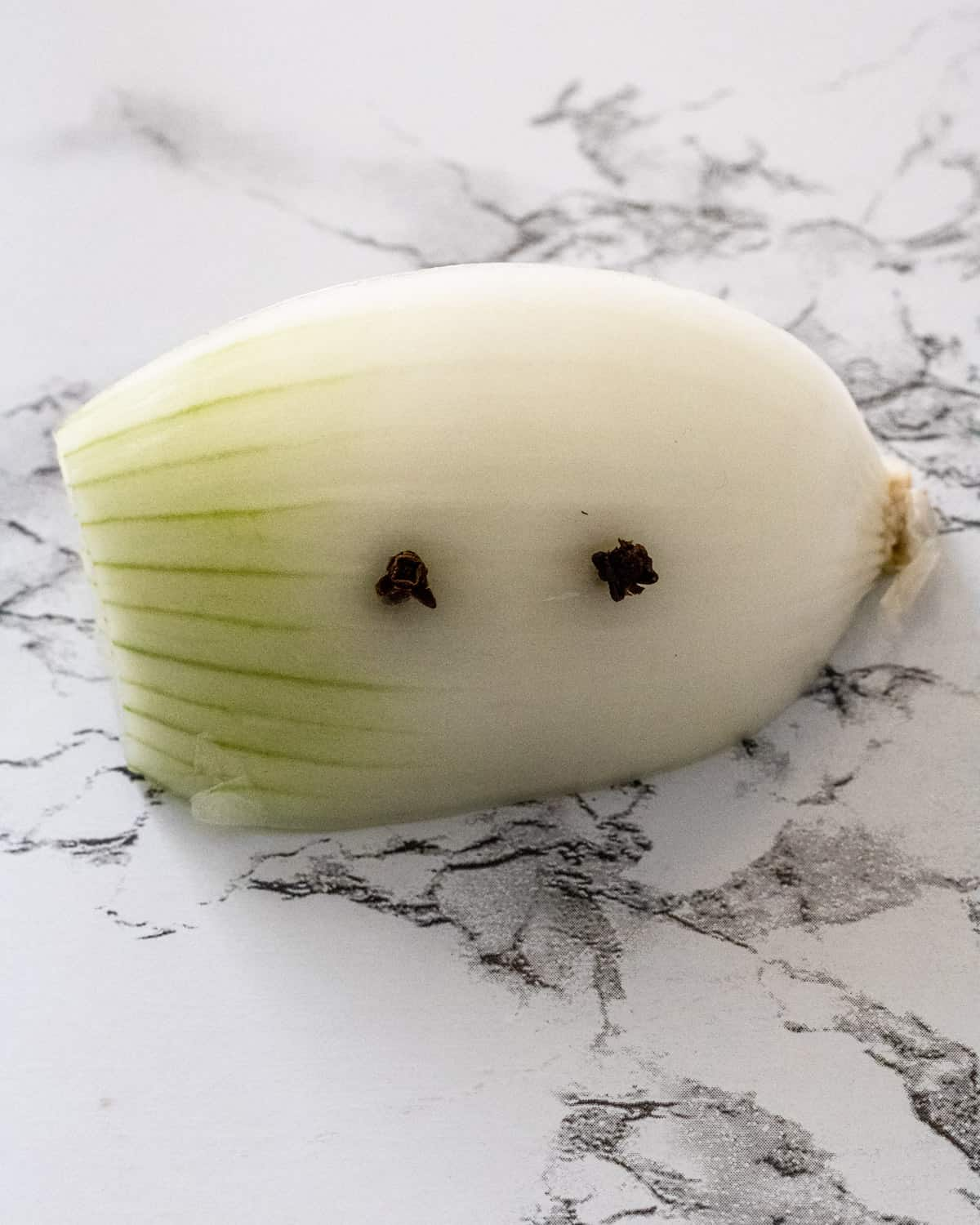 Onion with two cloves stuck into the side.