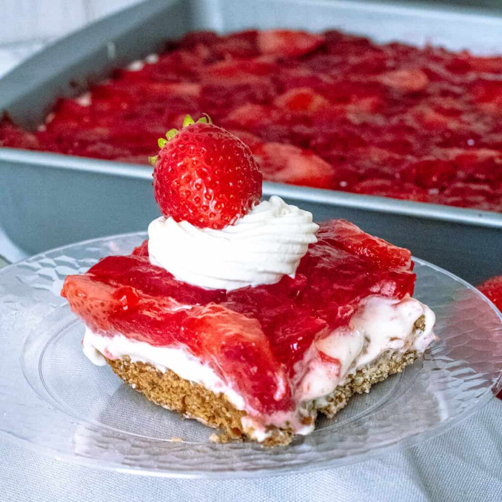 Square of strawberry salad on a plate, with pan of jello salad behind it.
