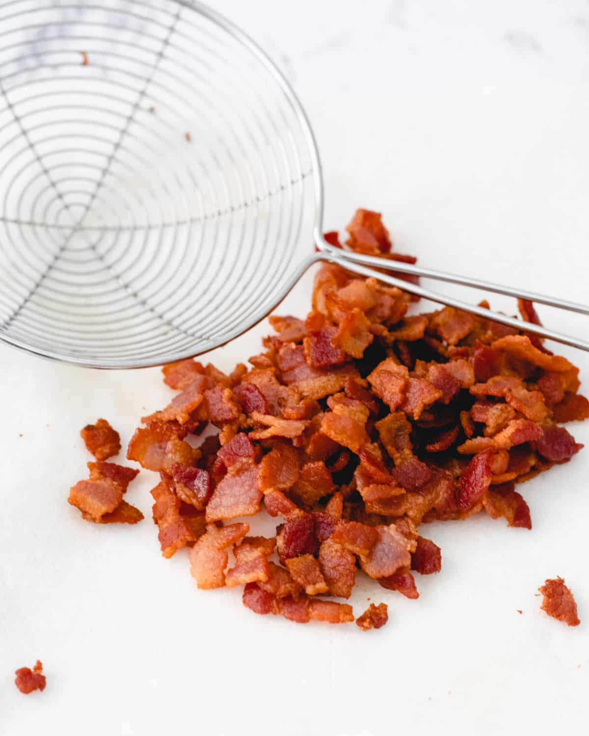 Crumbled crispy bacon with a wire scoop resting next to it.