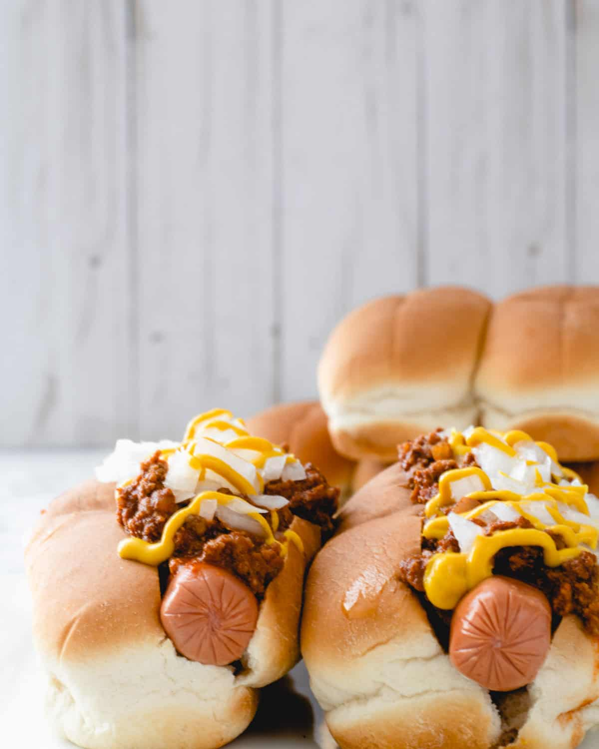 Two coney dogs with a pile of buns behind them.