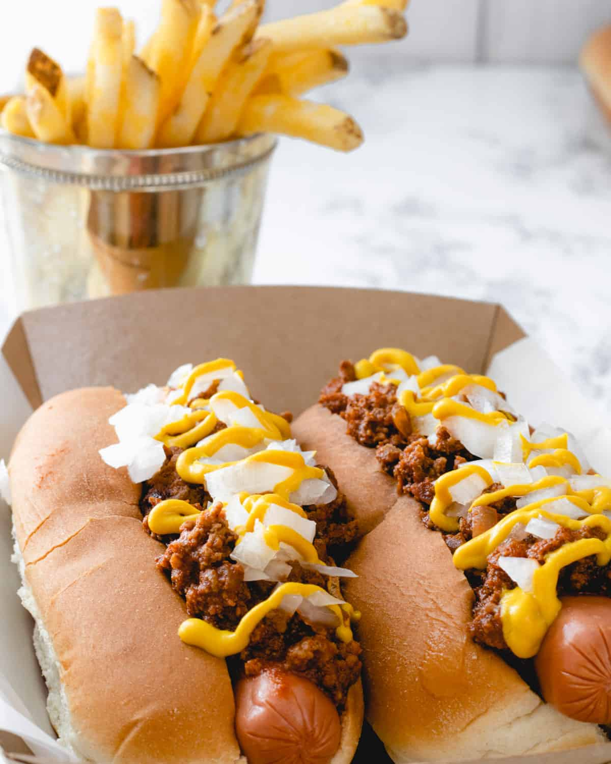 Two coney dogs with French fries behind them.