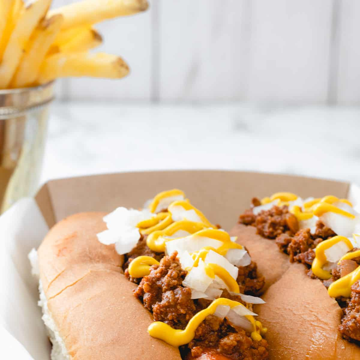 Two coney dogs, a famous food from Michigan, along with French fries.