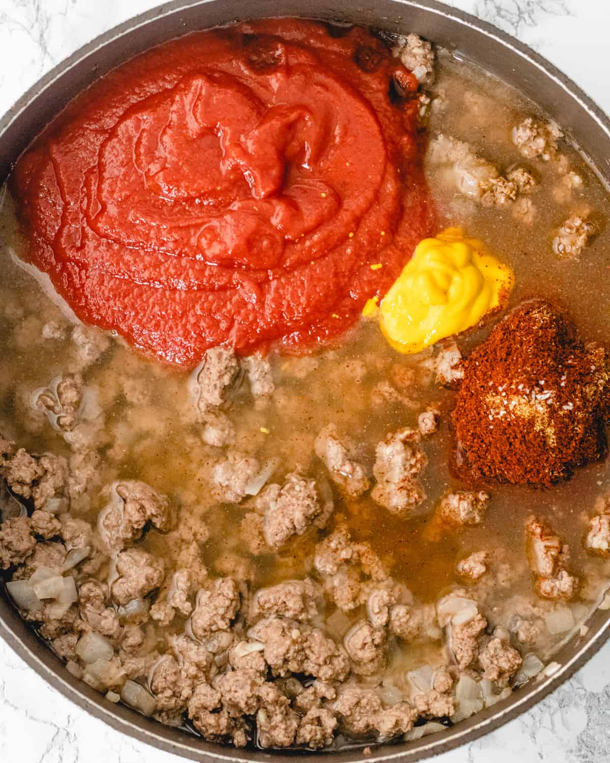 Tomato puree, spices, and other ingredients in the pan with cooked beef.