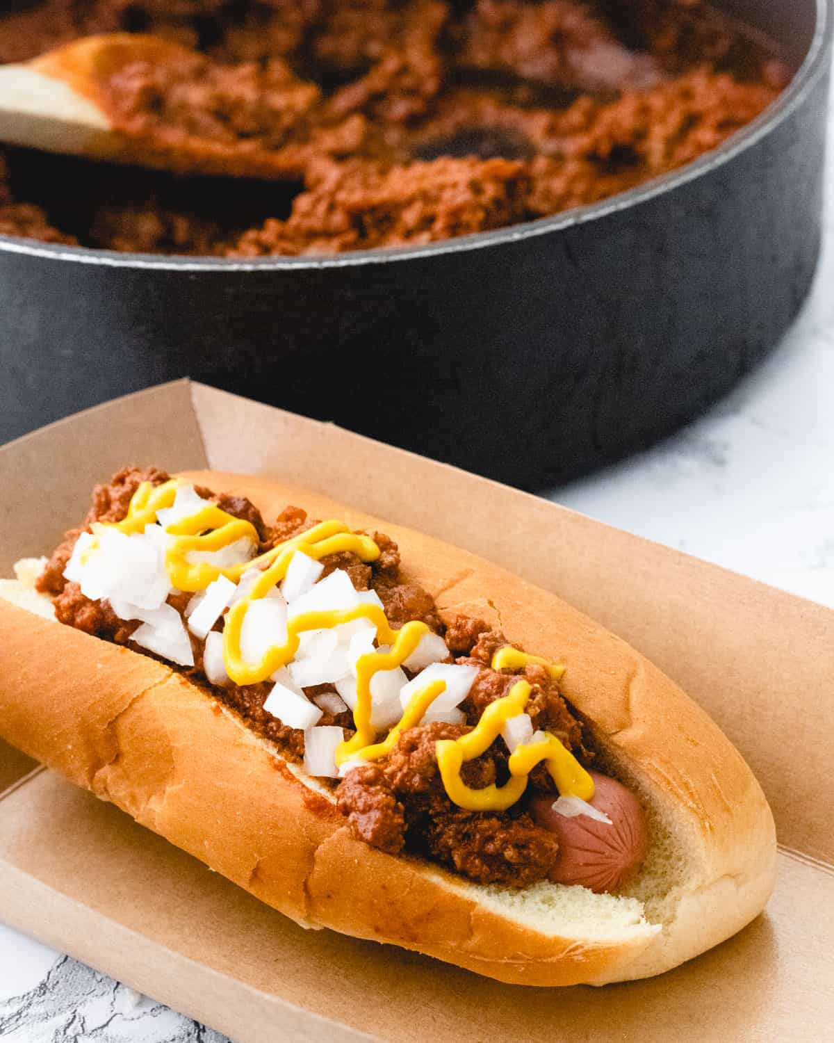 A coney dog in a cardboard holder with pan of chili sauce behind it.