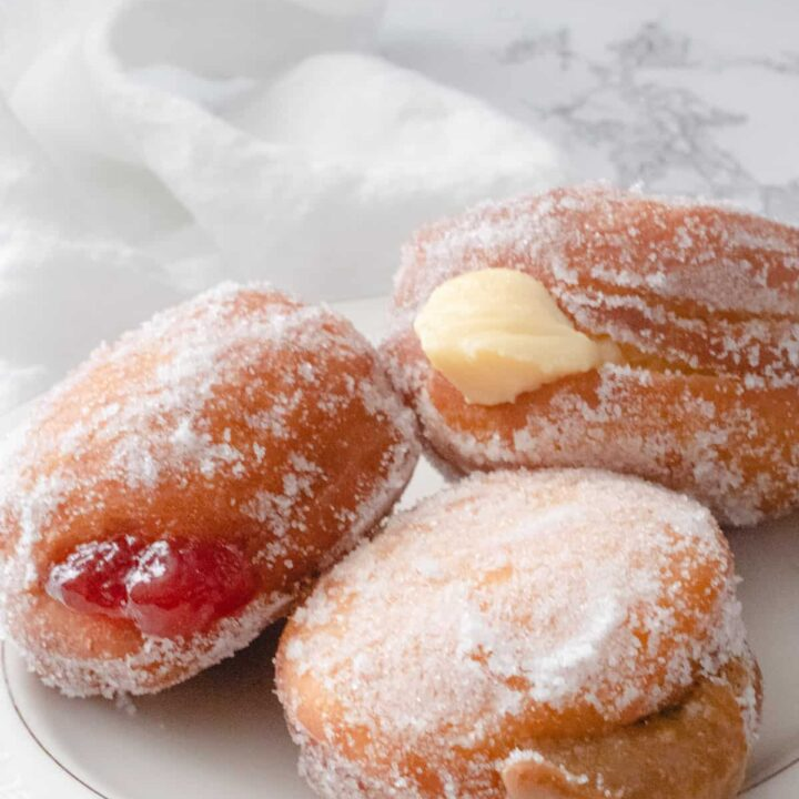 3 paczki donuts, 1 with strawberry filling, 1 with cream, and 1 with dulce de leche.