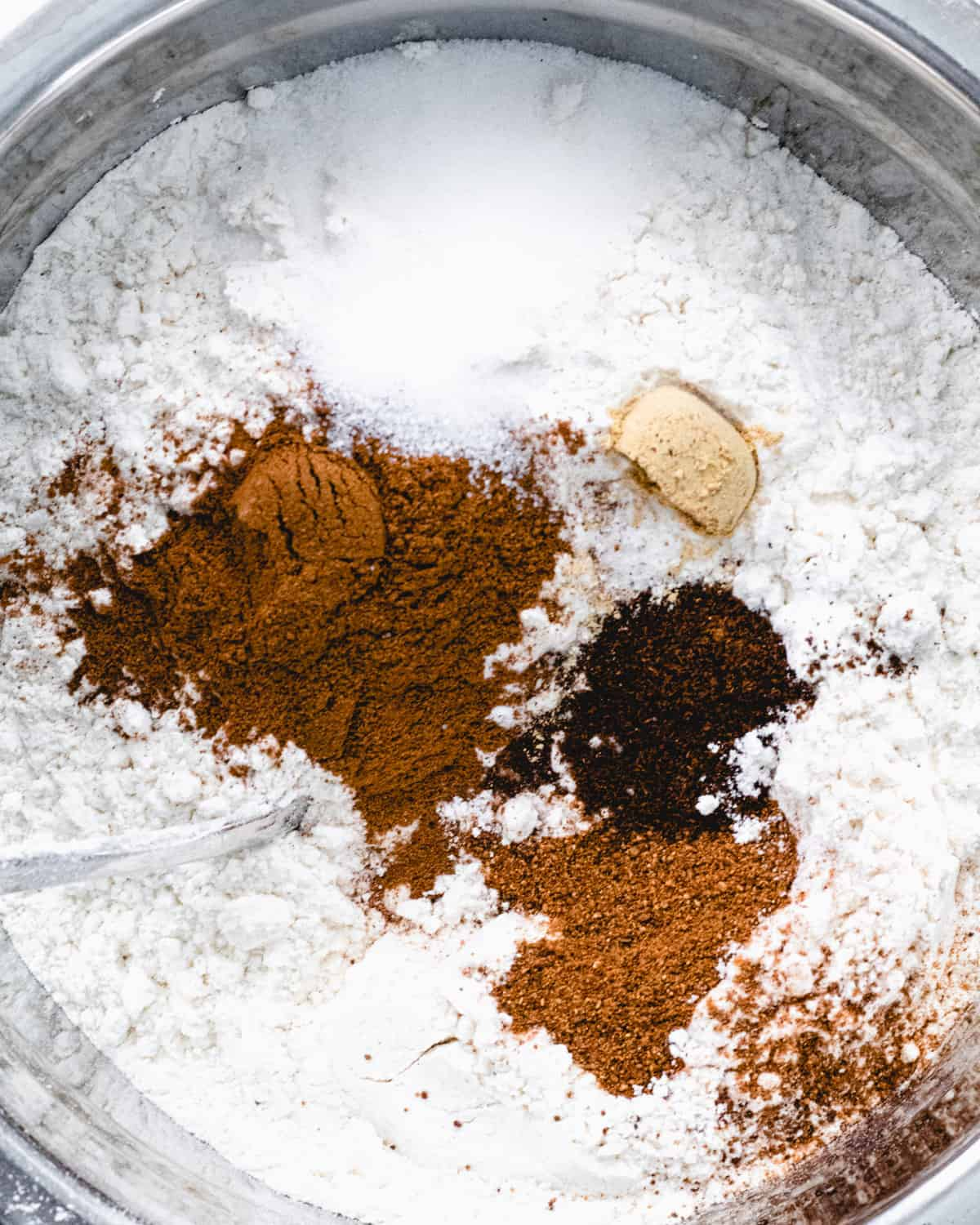 Bowl of flour with all of the spices on top.