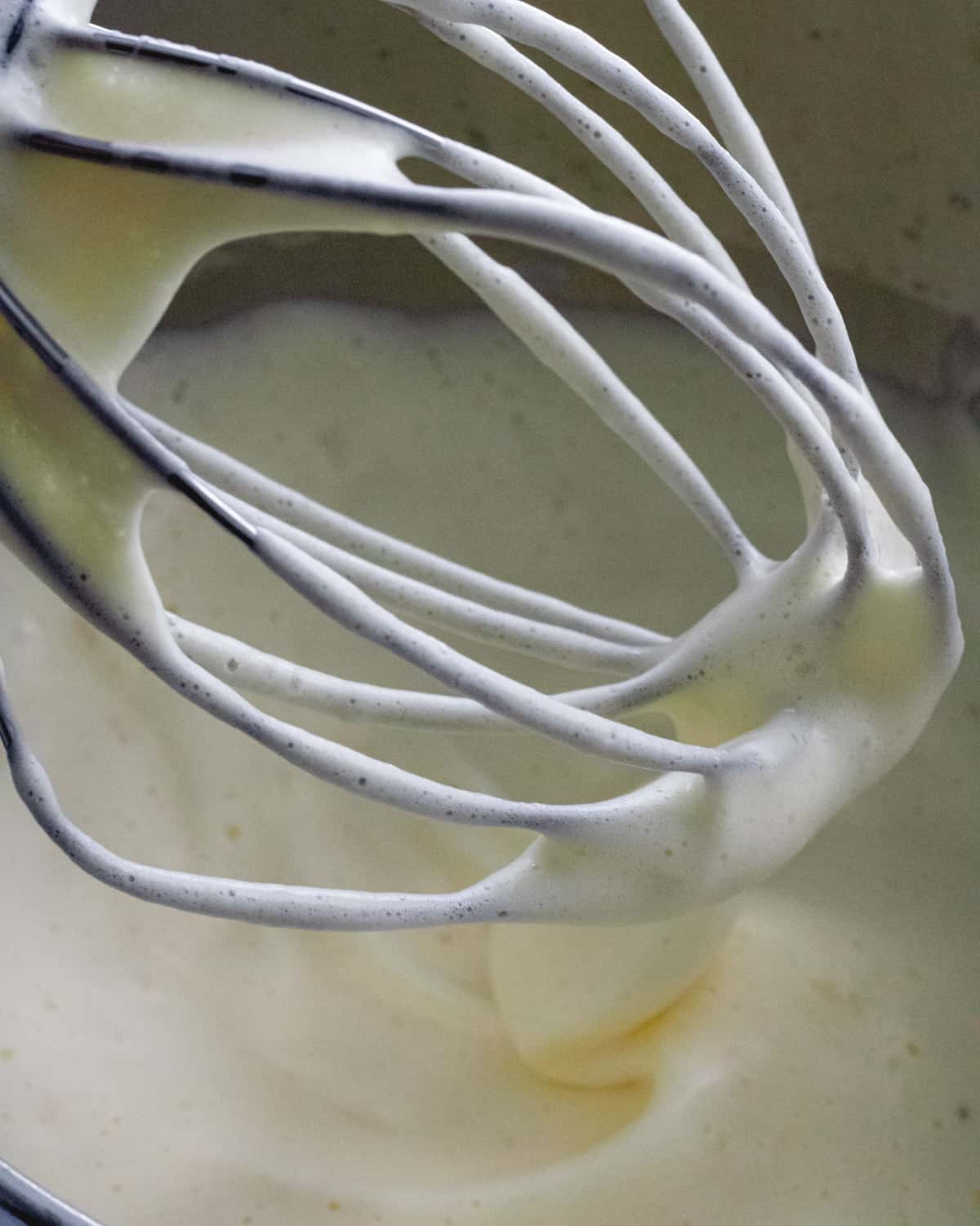 Whisk held above bowl of eggs. Eggs are fluffy and pale yellow.