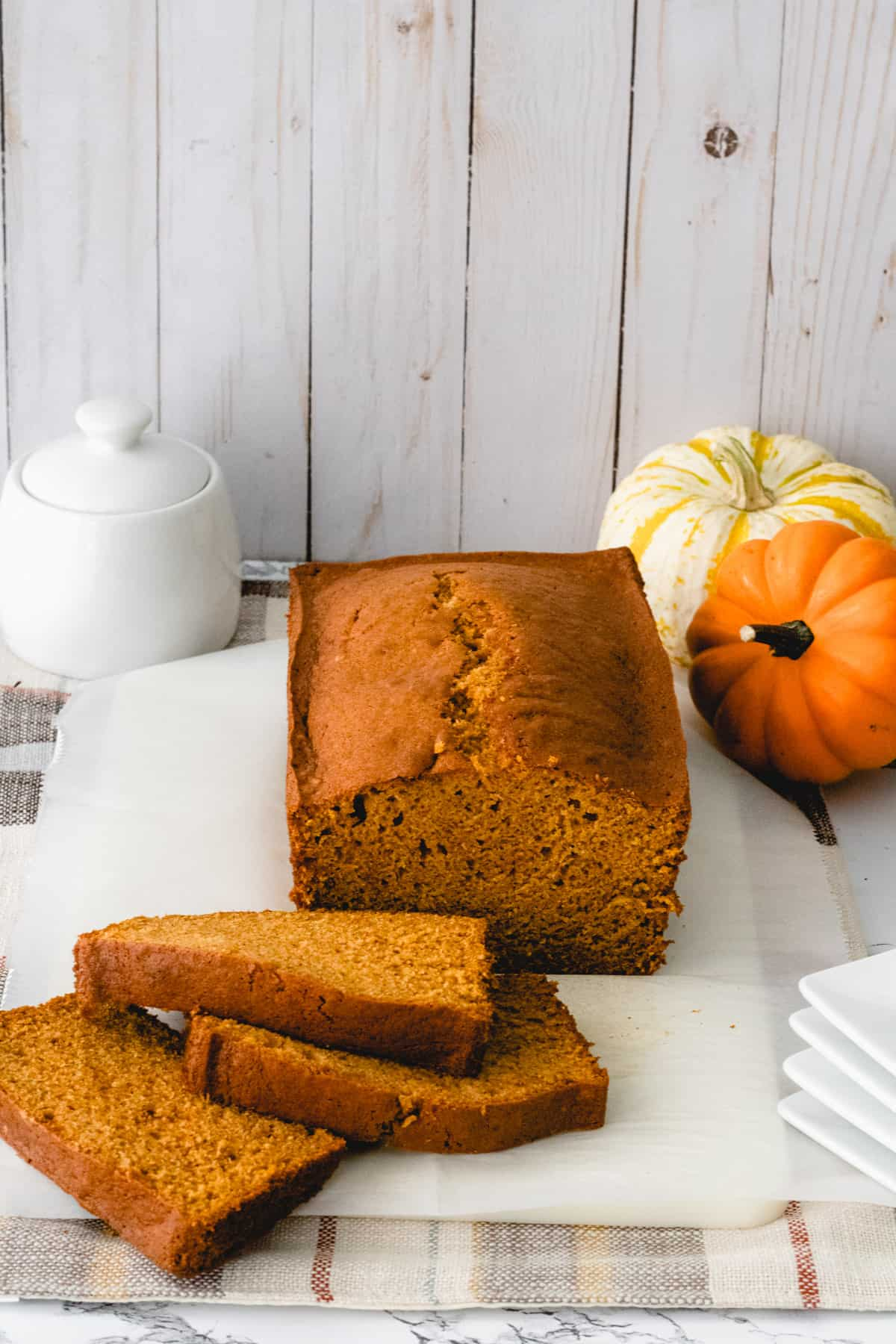 Applesauce pumpkin bread with 3 slices stacked to the left. Pumpkins and sugar jar in back corners.