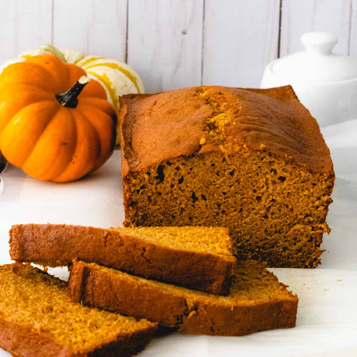 Square image of pumpkin bread with 3 slices on the side, stacked offset.