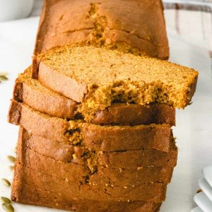 Pumpkin bread with slices stacked in front. There is a bite out of the top slice.