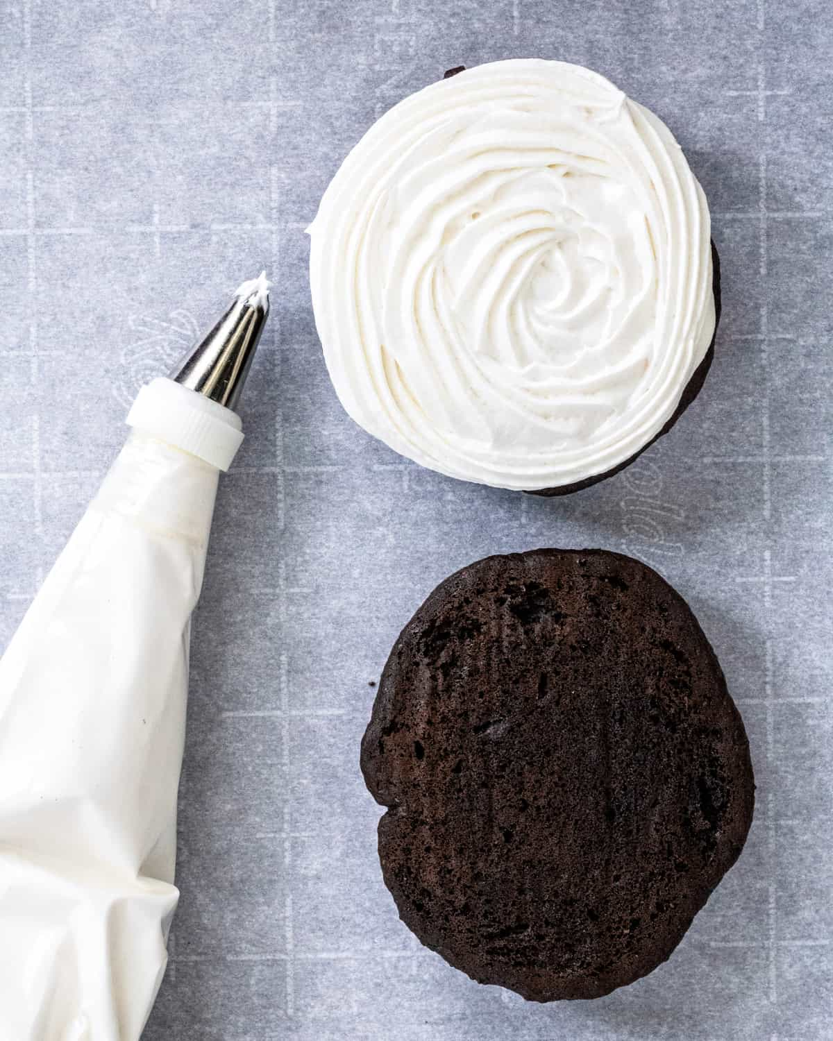 A Whoopie Pie with the top off, and a piping bag of filling next to it.
