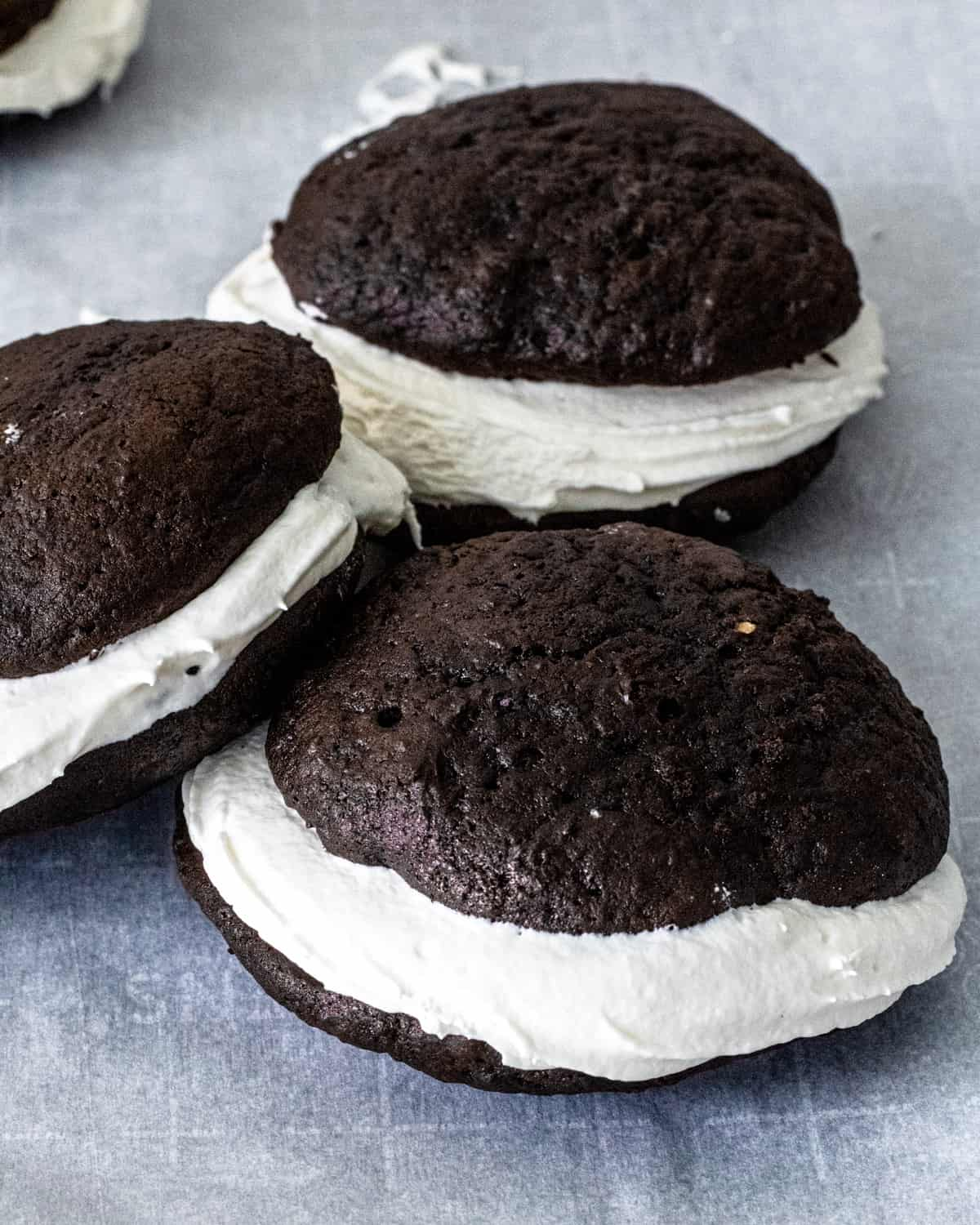 Three Whoopie pies on a parchment sheet with one of them shingled on another.