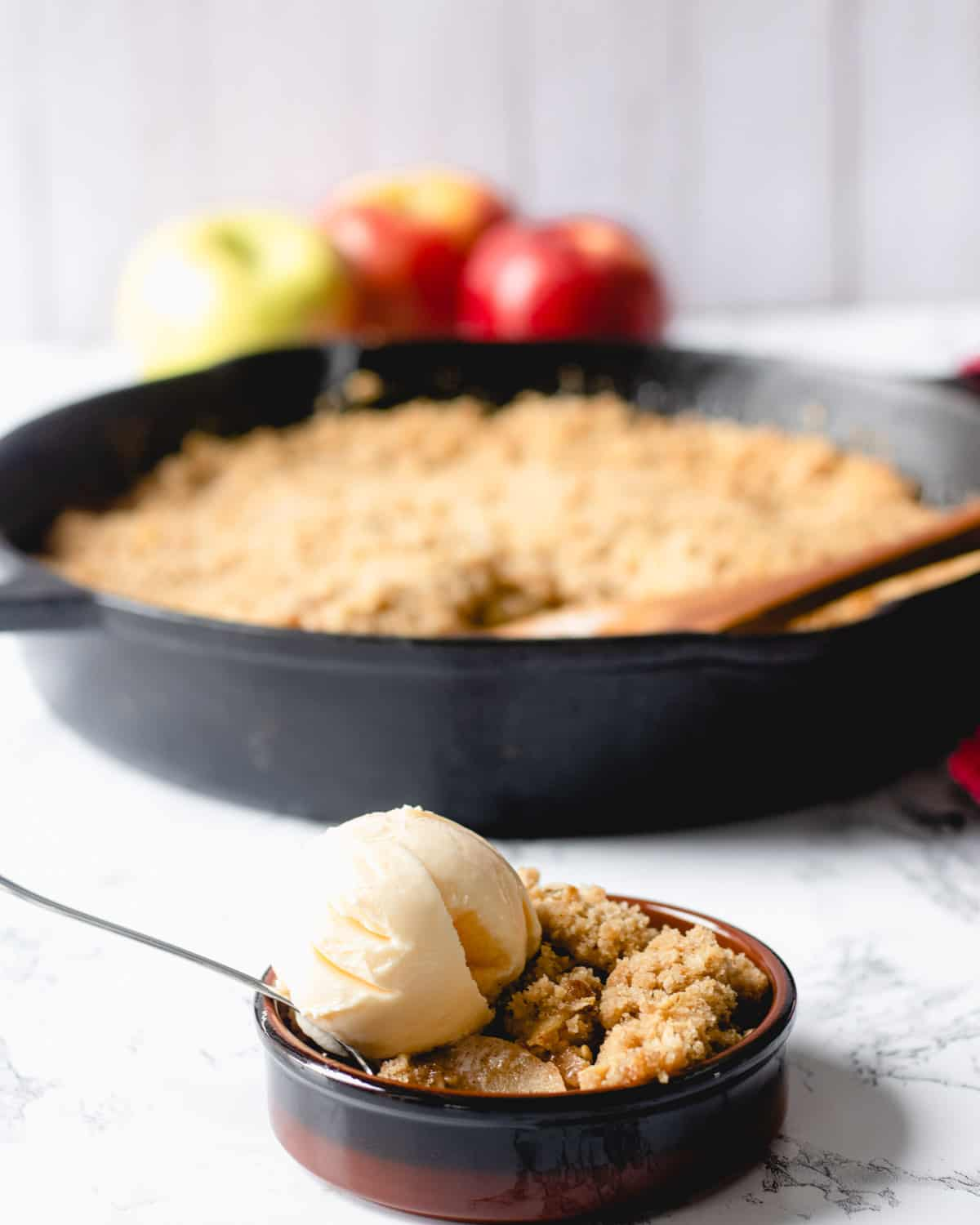 Ramekin of skillet apple crisp with ice cream, skillet of whole crisp in background, with apples behind them.