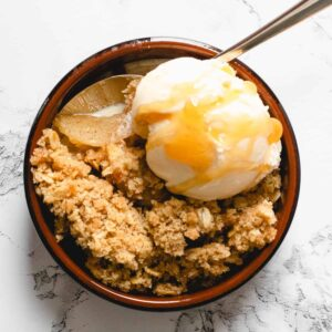 individual portion of apple crisp, topped with ice cream and caramel sauce.