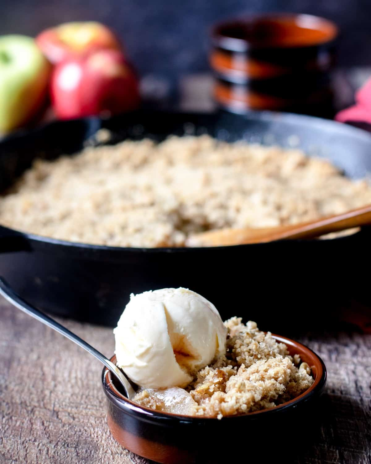 Ramekin of apple crisp topped with ice crema, and a skillet of apple crisp in the background.