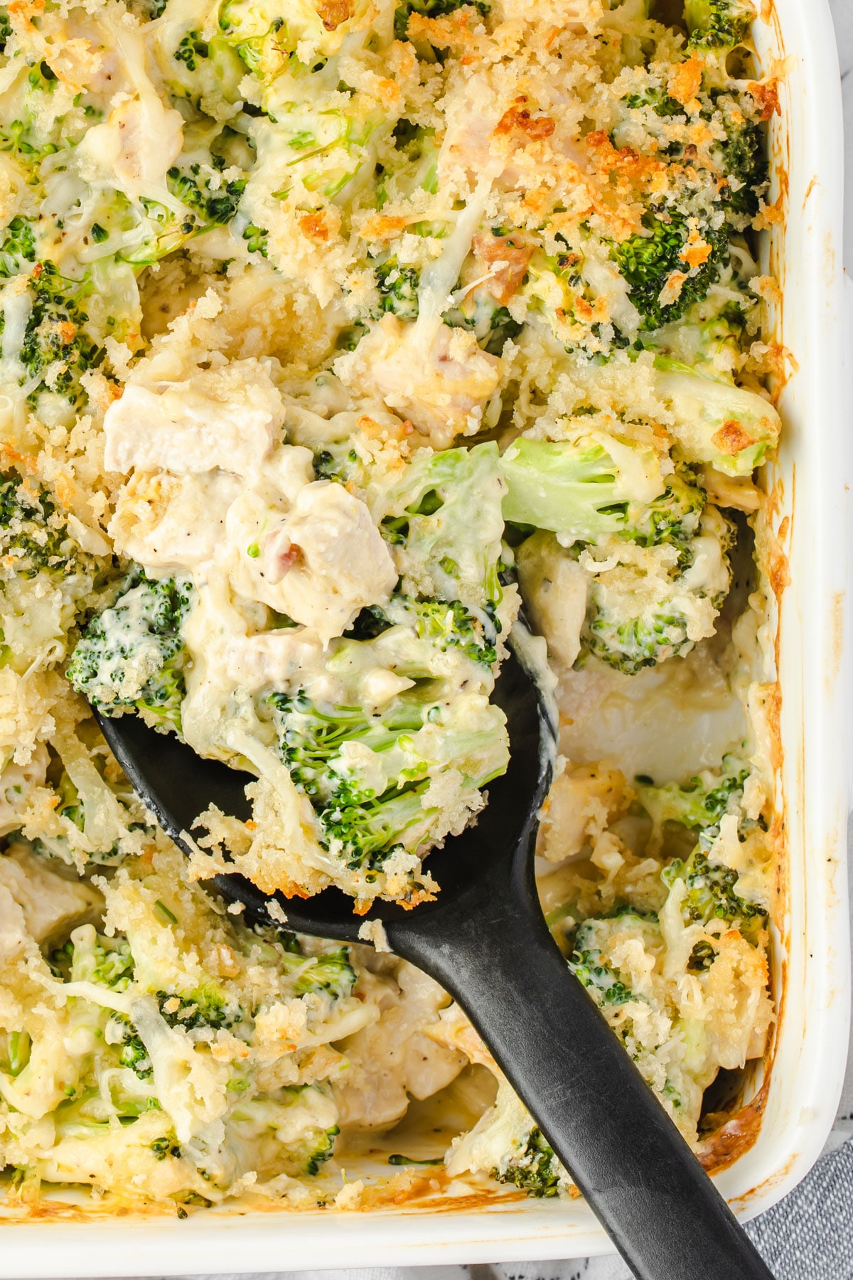 broccoli & chicken casserole scooped with a black spoon.