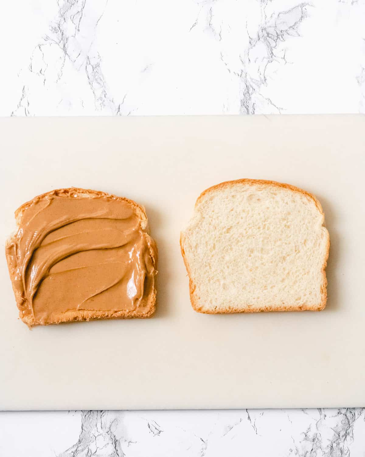 Peanut butter on one slice of bread on the left, and a plain piece of bread on the right.