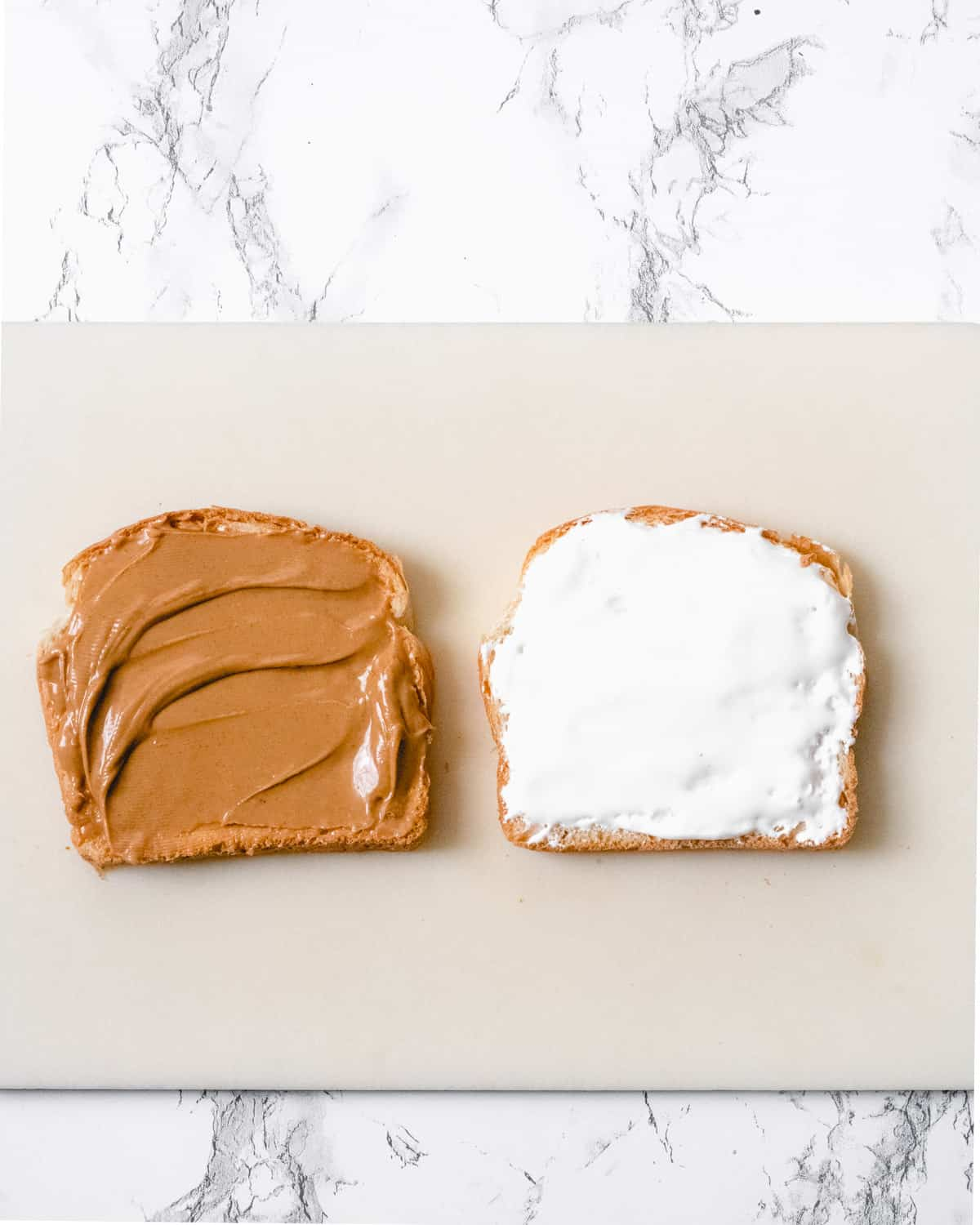 Peanut butter spread on bread on the left, and fluff on the piece of bread on the right.