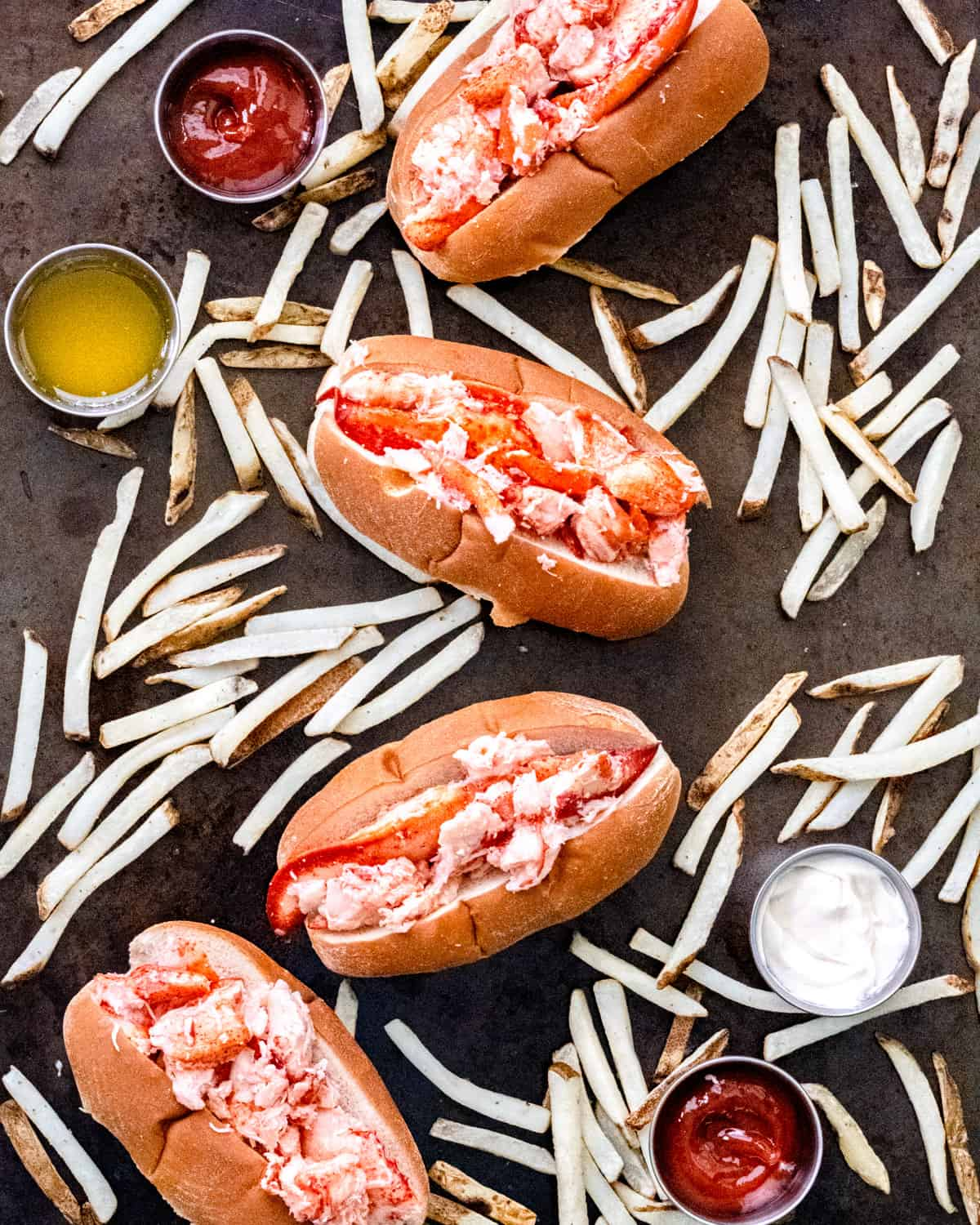 4 lobster rolls on a sheet pan with fries and condiment ramekans.