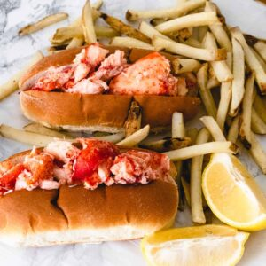 2 lobster rolls with fries and 2 lemon wedges.