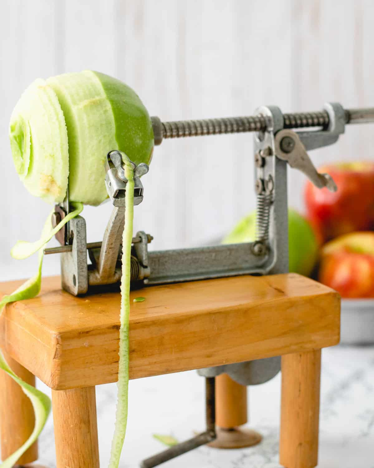 Granny smith apple, half peeled on an apple peeler, corer, slicer.