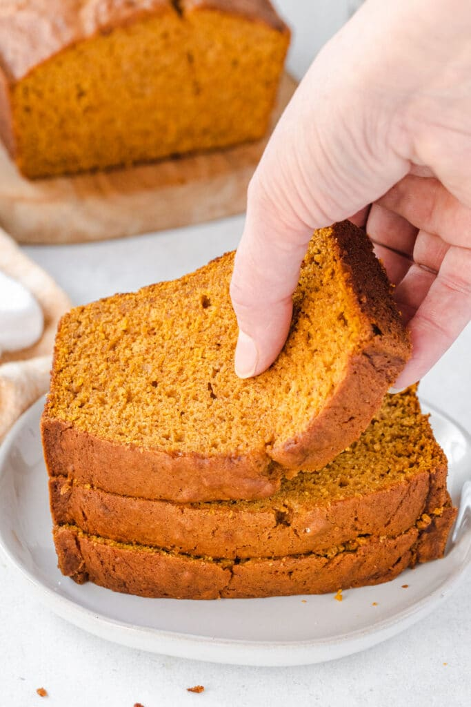 Someone taking the top slice of a stack of 3 pumpkin bread slices.